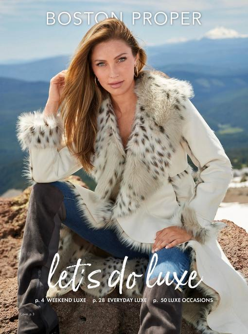 model wearing a white animal print faux fur coat, jeans, silver hoops, and gray over-the-knee boots.