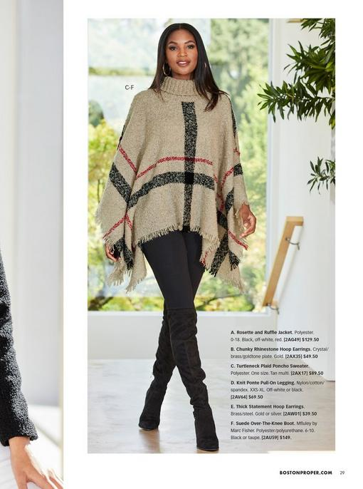 model wearing a beige plaid turtleneck poncho sweater, black leggings, black over-the-knee boots, and gold hoop earrings.