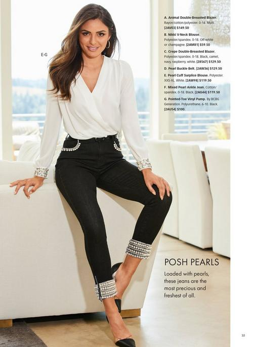 model wearing a white surplice embellished cuff top, black pearl embellished jeans, and black vinyl heels.