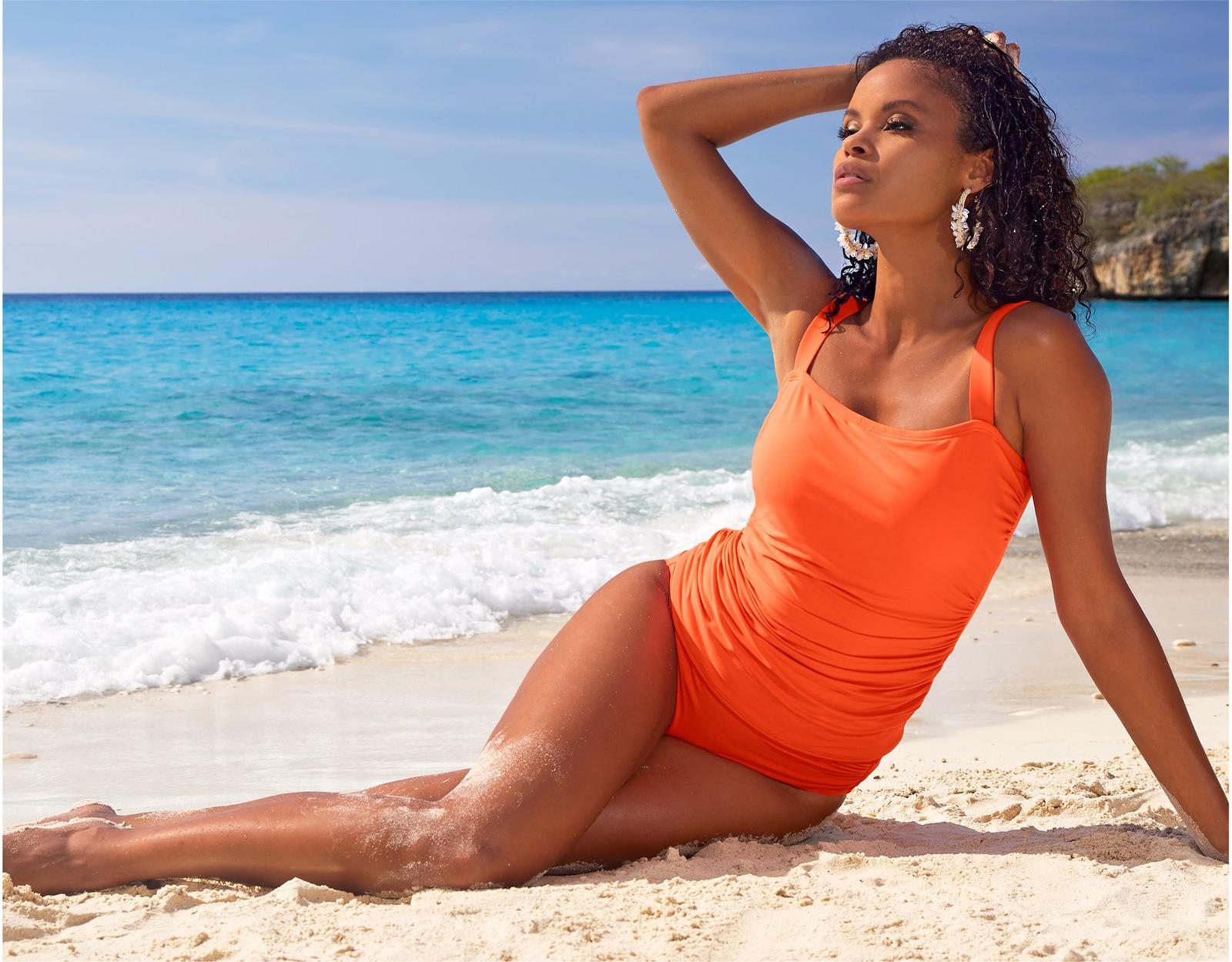 model lounging on the beach wearing a coral tankini with high-waisted bikini bottoms.