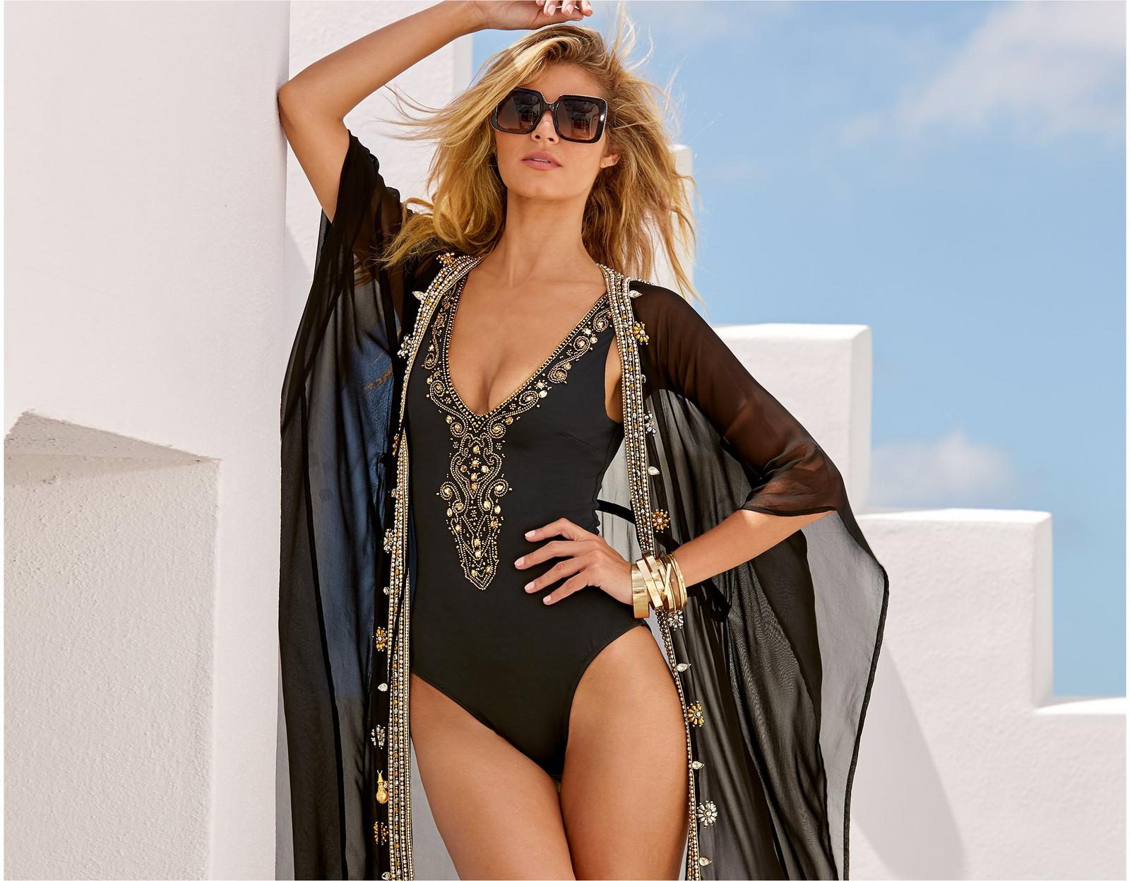 model wearing a black one-piece swimsuit with gold embellishments with the matching cover-up and statement sunglasses.