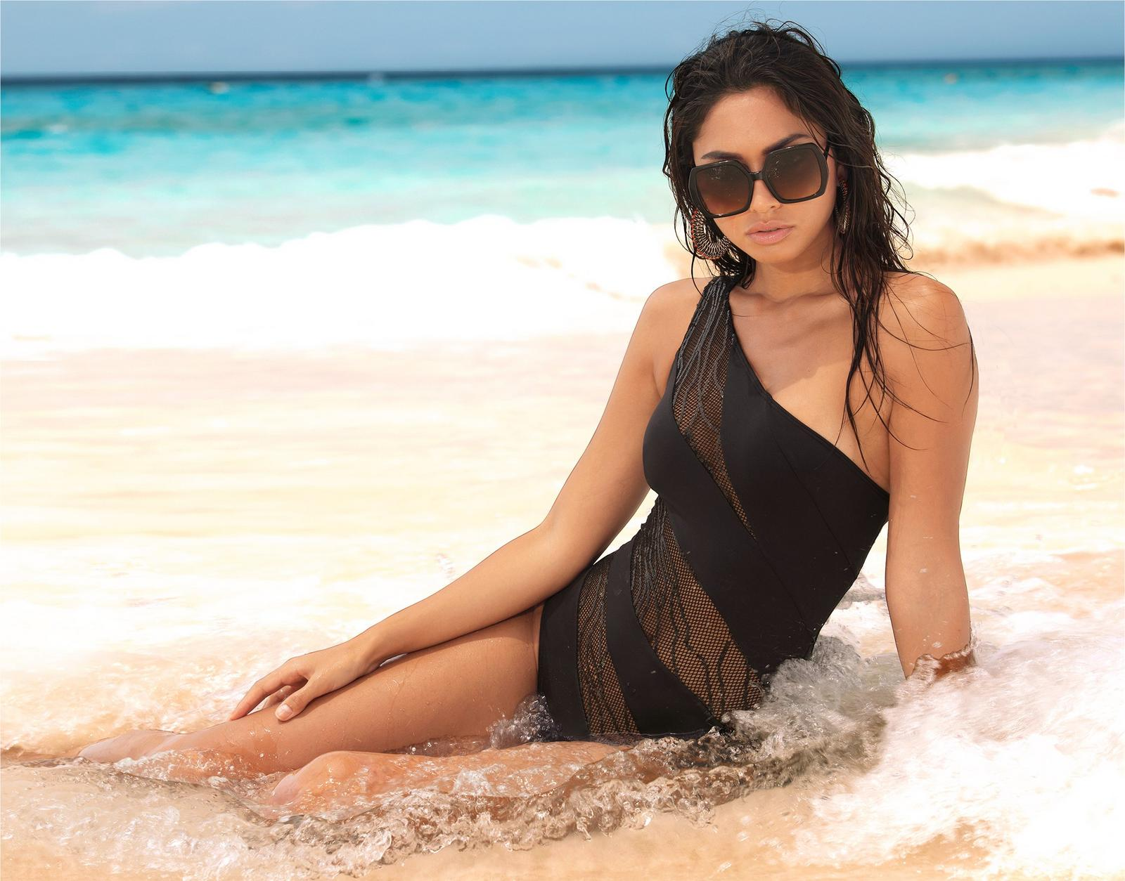 model lounging on the beach wearing a black and mesh one-shoulder one-piece swimsuit and statement sunglasses.