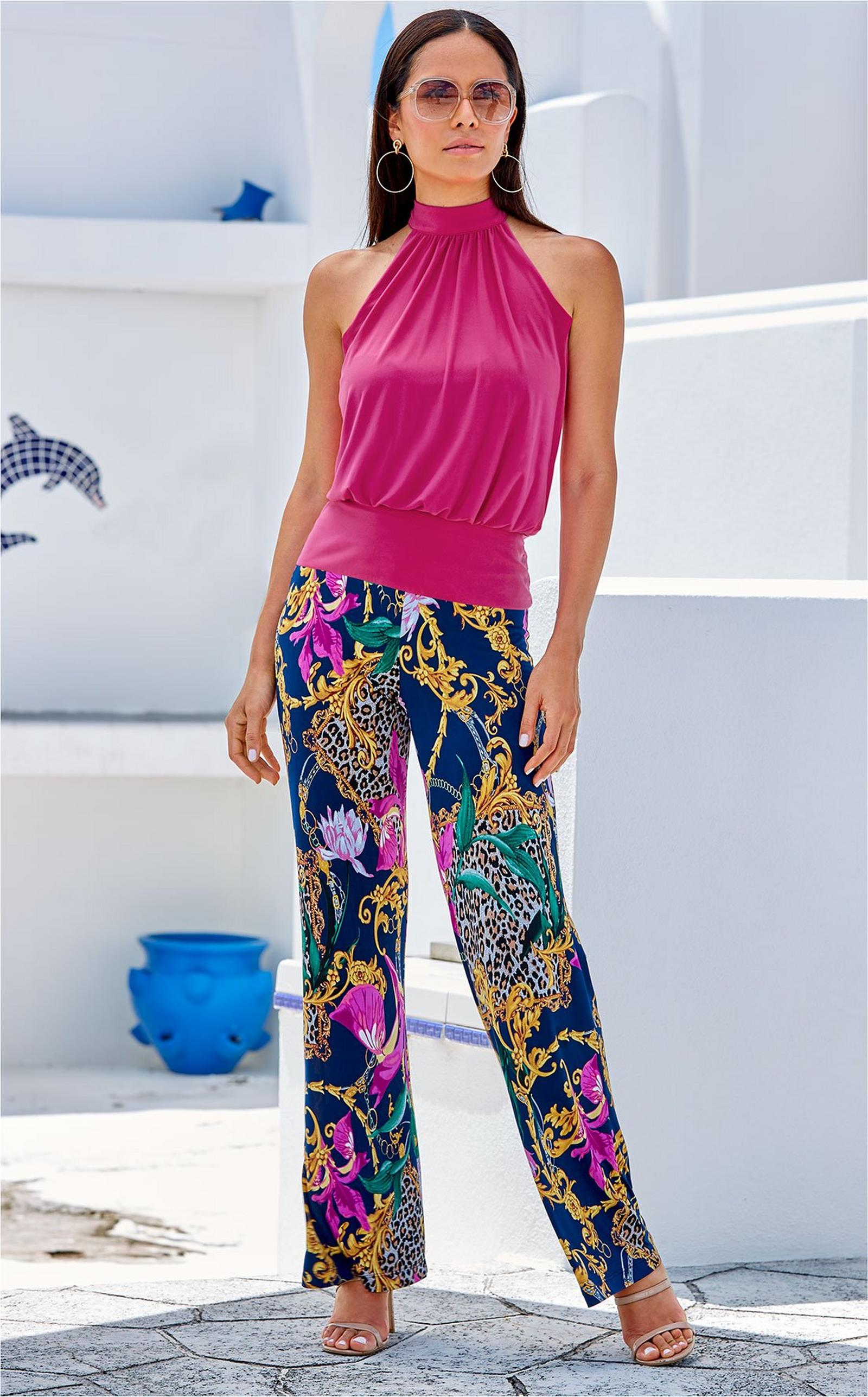 model wearing a mock-neck pink top and scroll animal print pants with sunglasses.