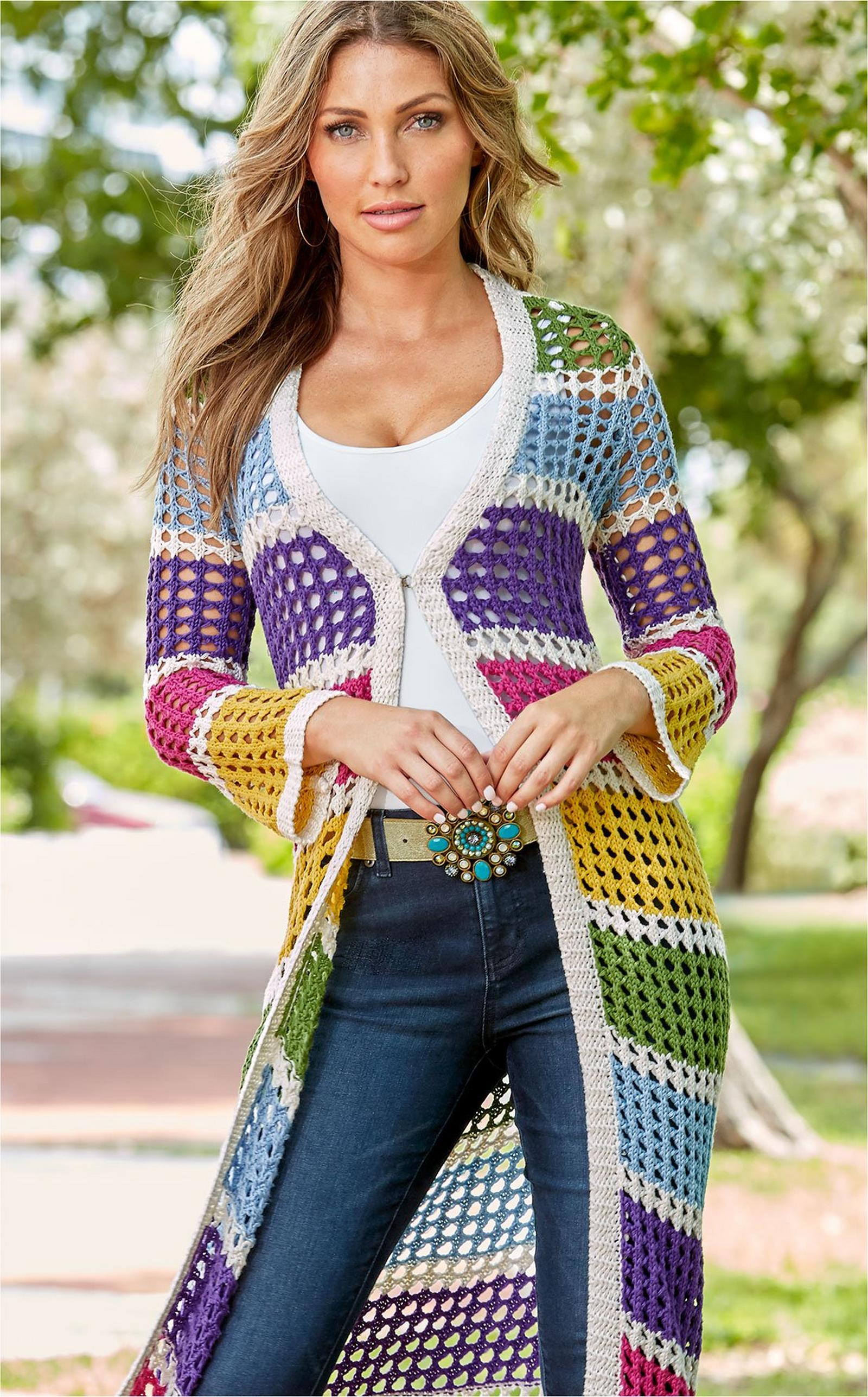 model wearing a multicolored crochet duster over a white tank top, turquoise jewel belt, and jeans.