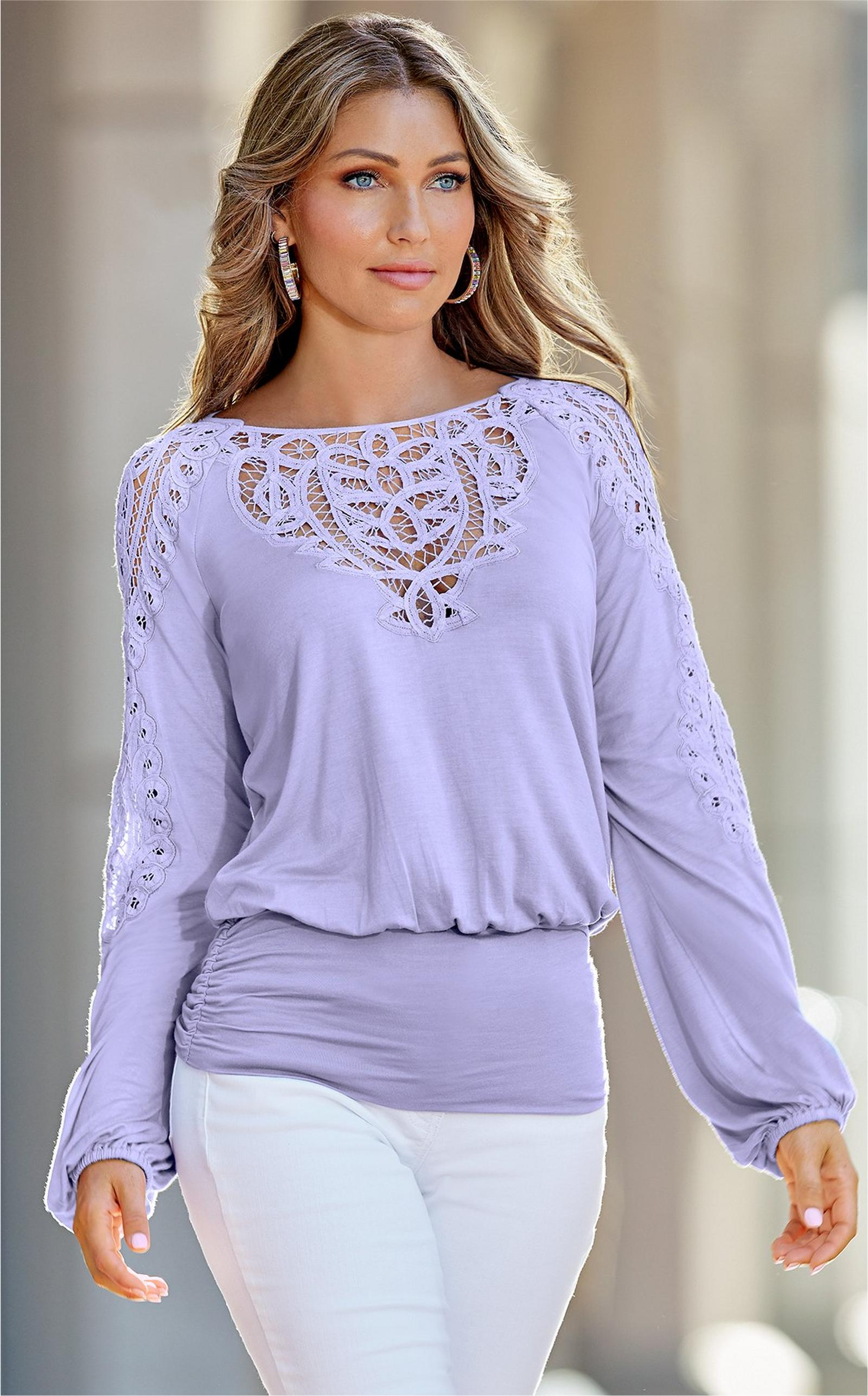 model wearing a pastel purple lace blouson top and white pants.