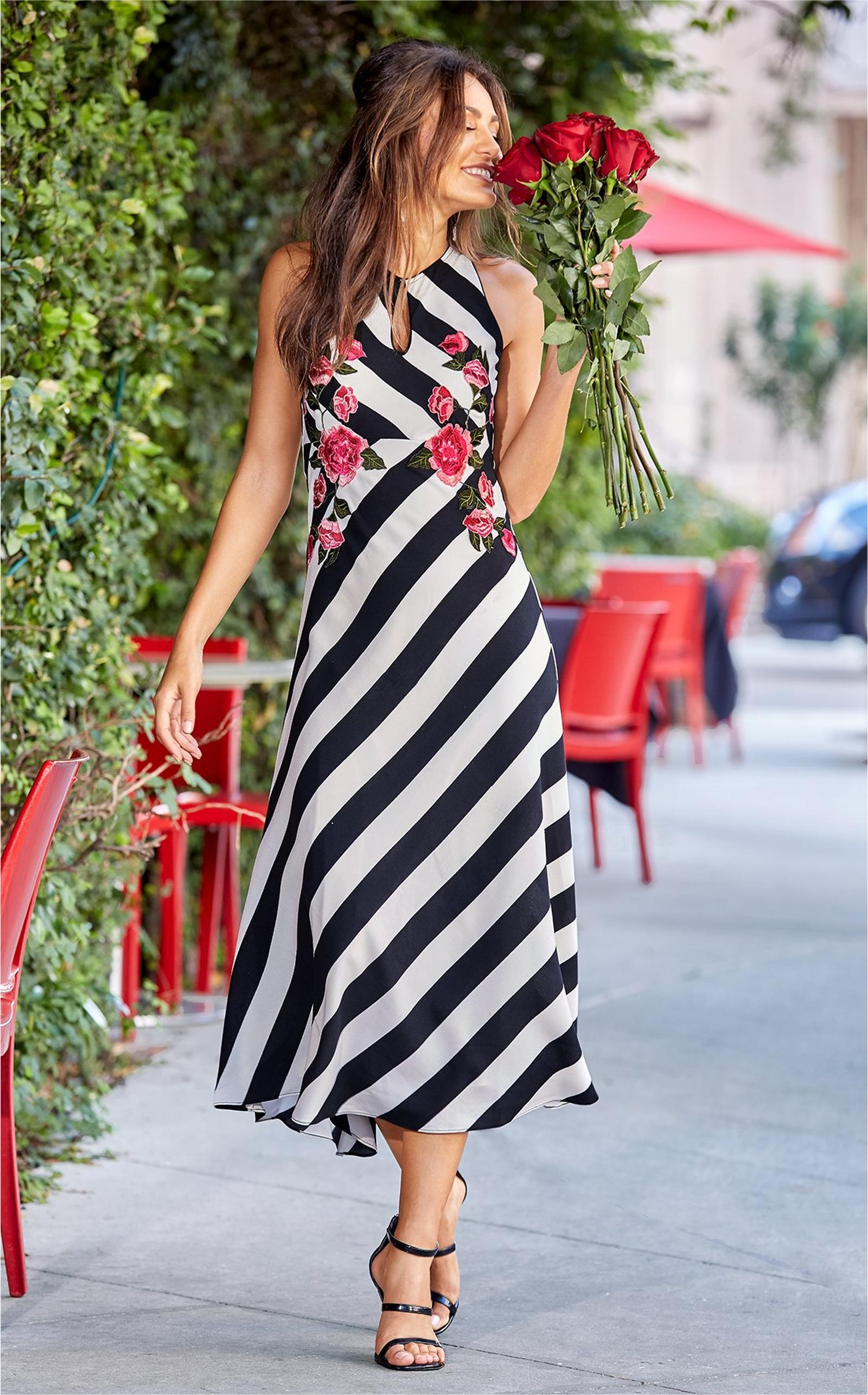 model wearing black and white striped midi dress with pops of pink flowers.
