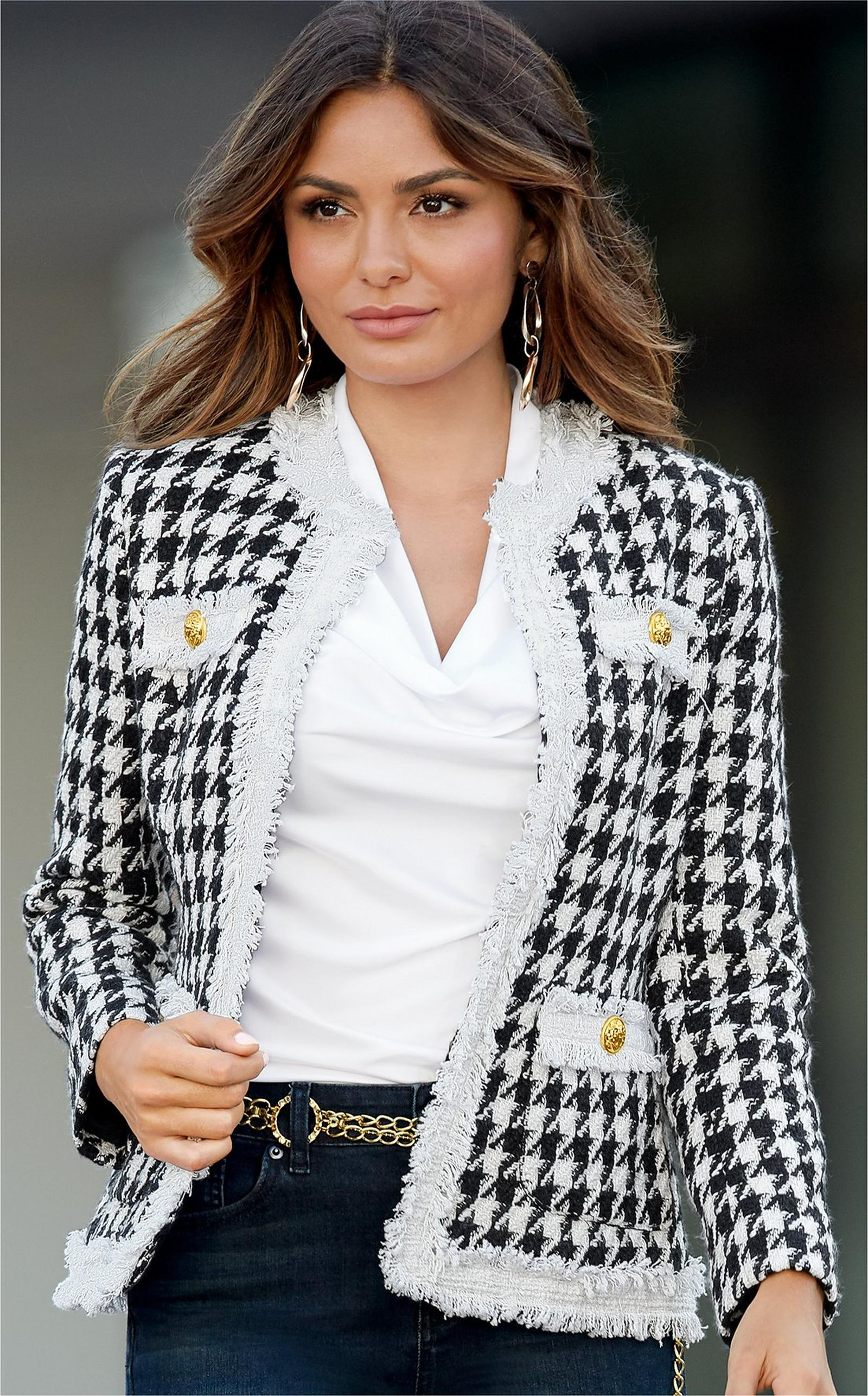 model wearing a black and white houndstooth tweed jacket over a white cowl neck top and jeans.