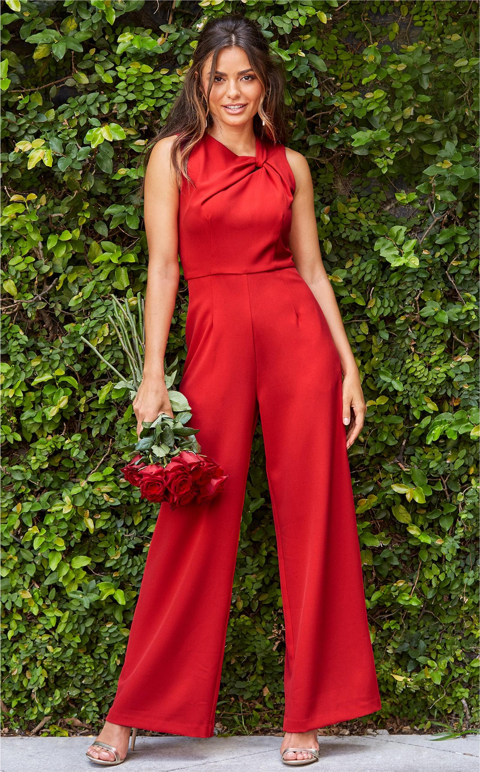 model wearing a red twisted jumpsuit while holding a bouquet of roses.
