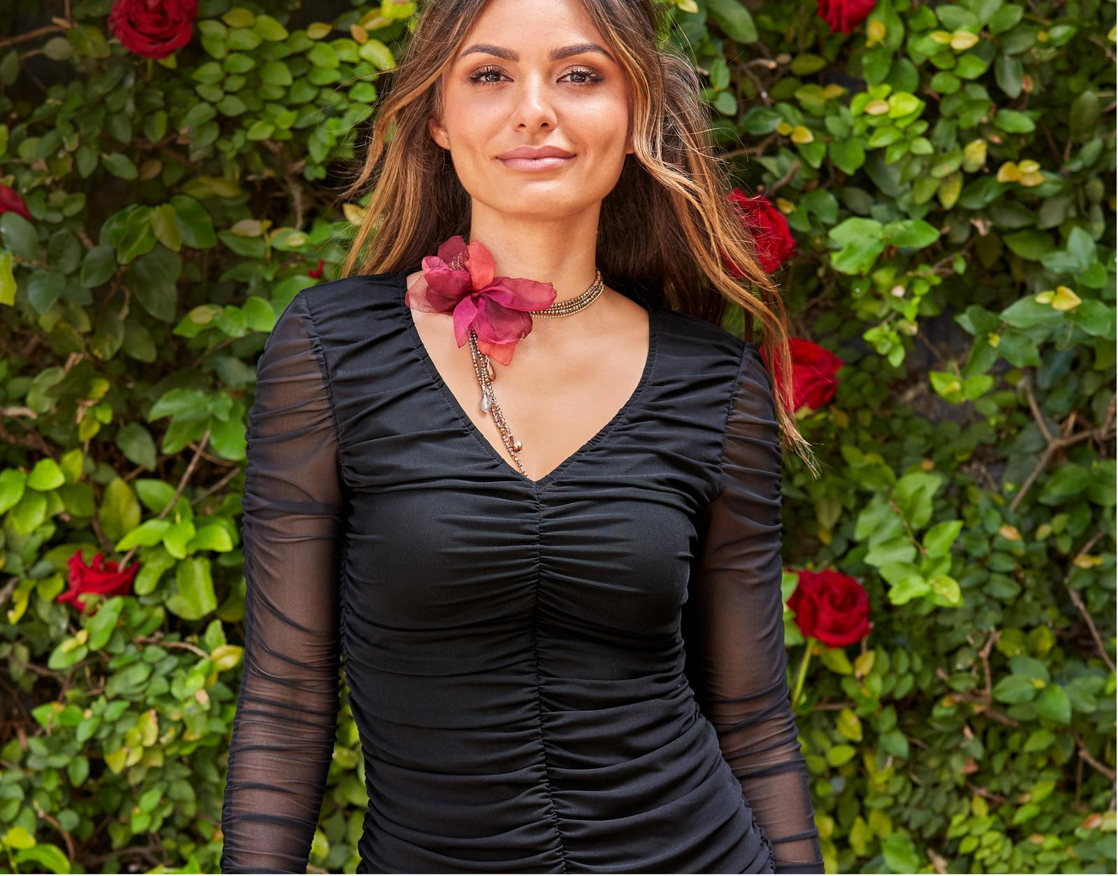 model wearing a ruched black long-sleeve top and a flower embellished choker.