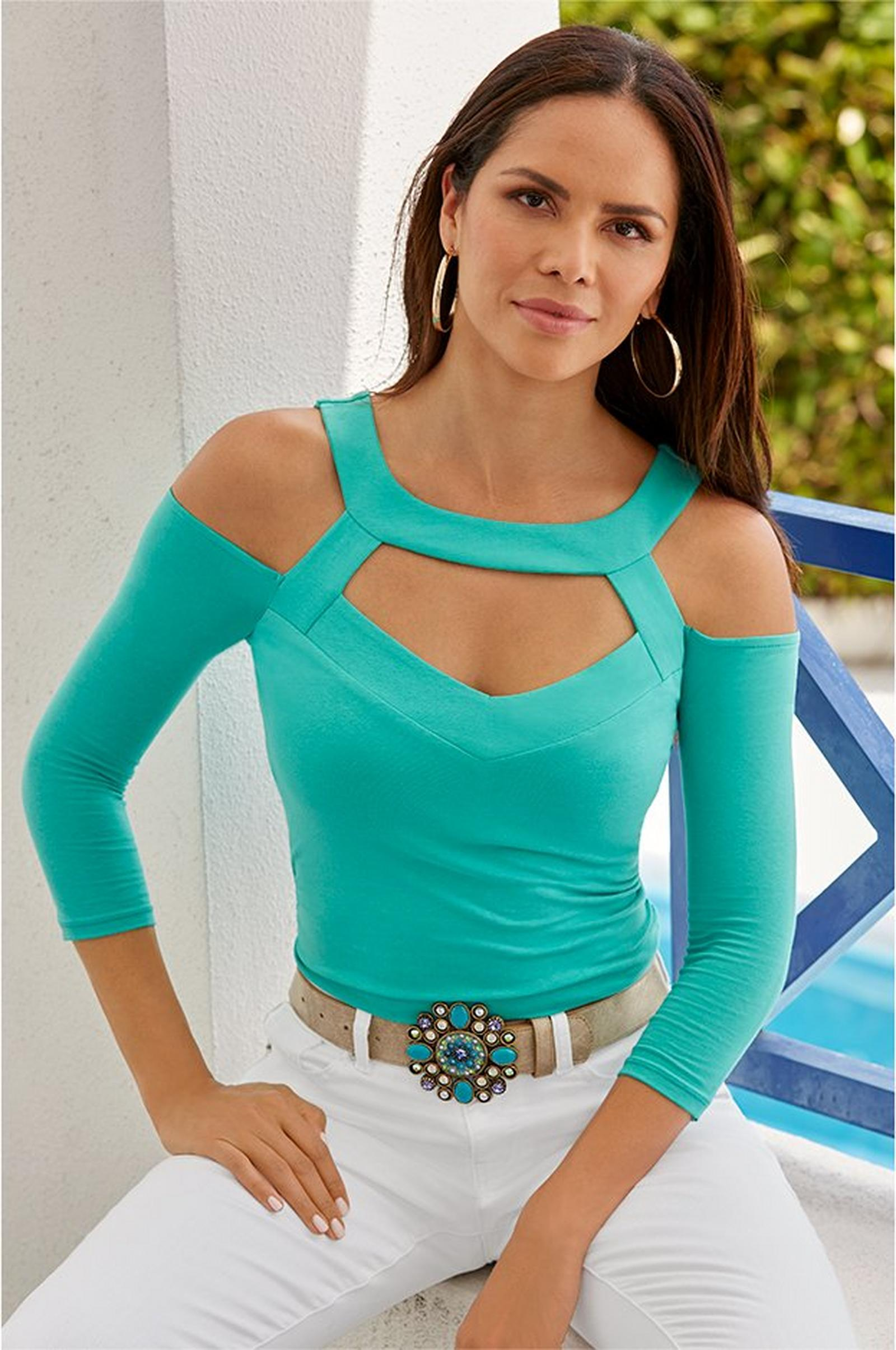model wearing teal cutout so sexy top with turquoise jewel belt and white pants.