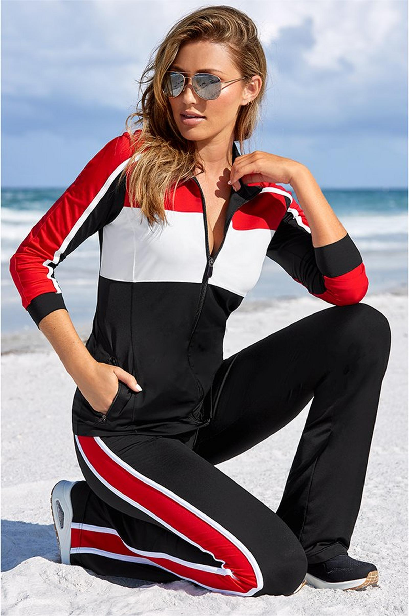 model kneeling on the beach wearing a red, black, and white color block sport coordinates.