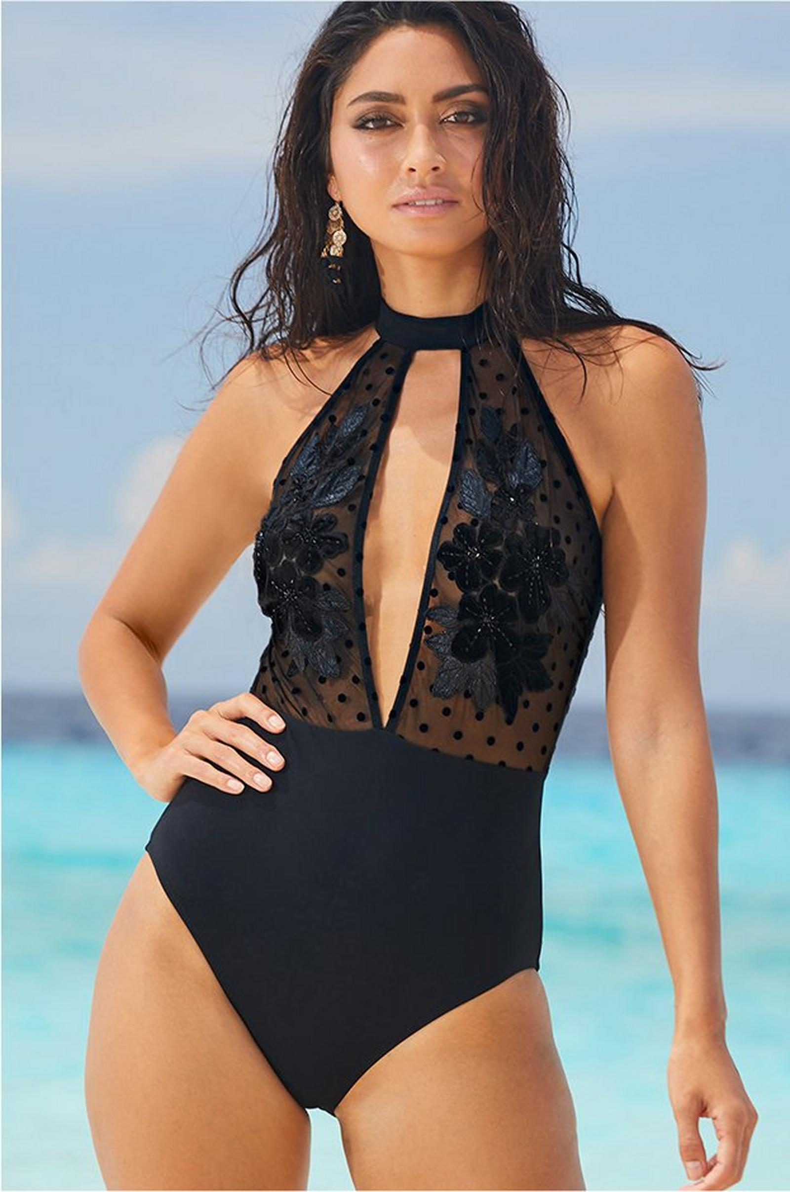 model wearing a sheer mesh floral embellished one-piece swimsuit in black.