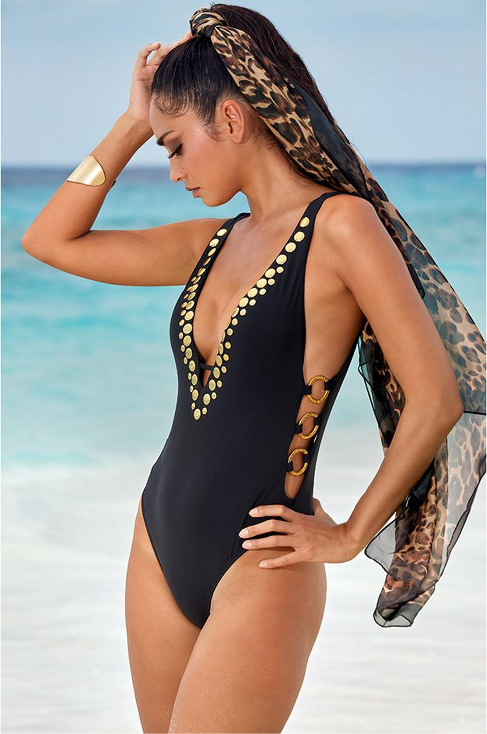 model wearing a gold embellished black one-piece swimsuit with a deep plunging neckline and a black and gold hair scarf.