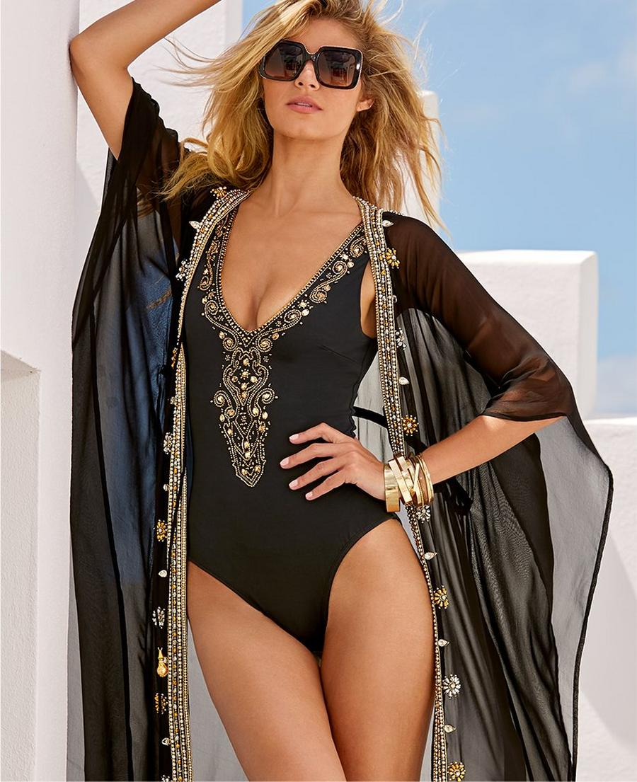 model wearing gold embellished black one-piece swimsuit and gold and black hair scarf.