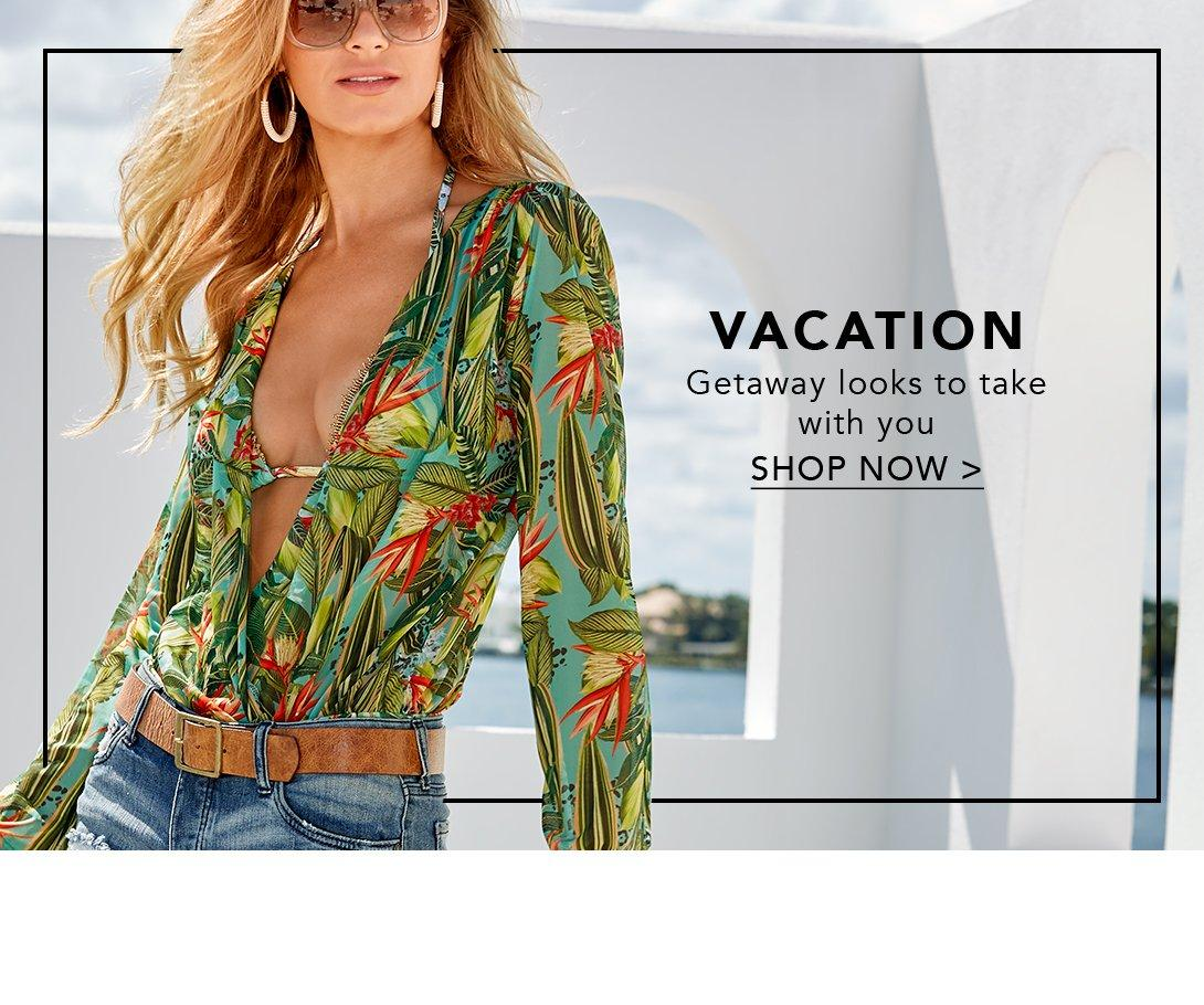 model wearing long sleeve jungle-print one-piece swimsuit with jean shorts and sunglasses.