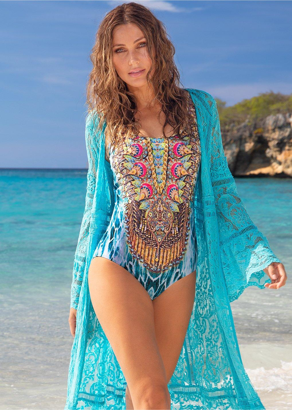 model wearing embellished one-piece swimsuit and a teal duster while standing on the beach.