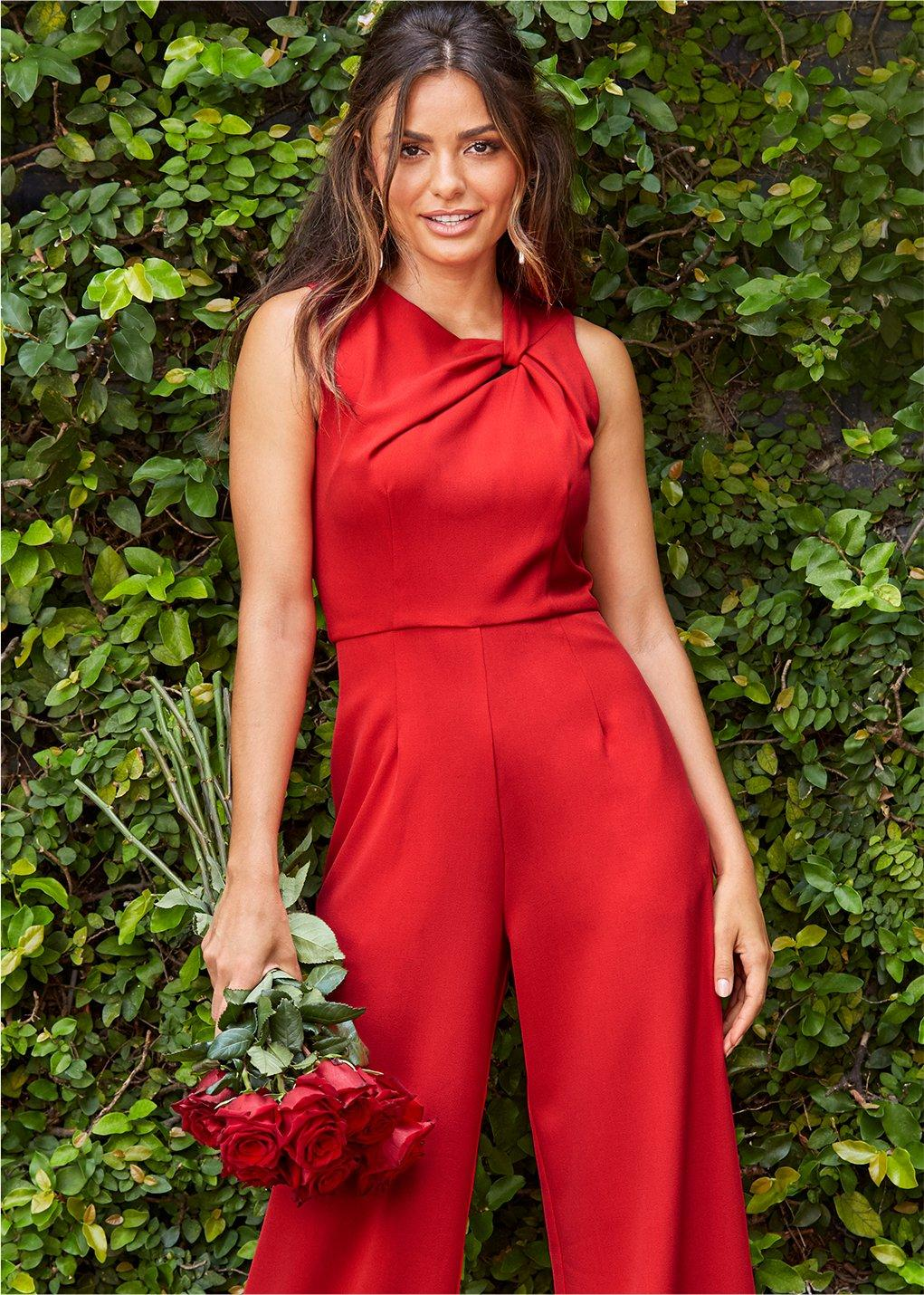 model standing in front of a hedge wearing red jumpsuit while holding a bouquet of roses.