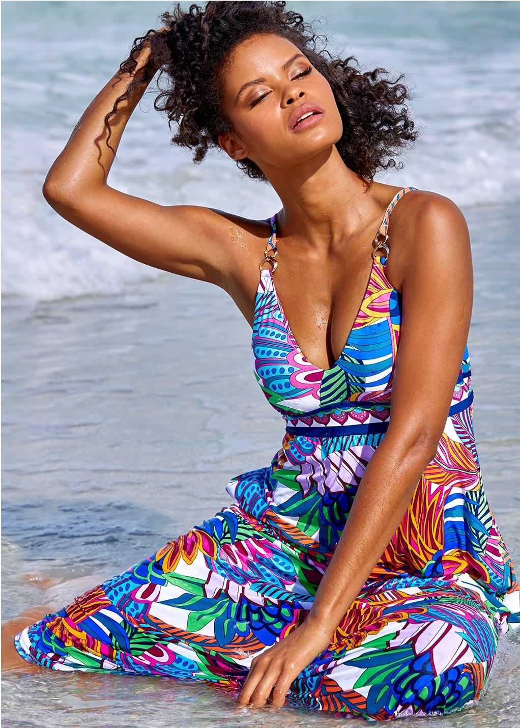 model lounging on the beach wearing a floral print maxi.