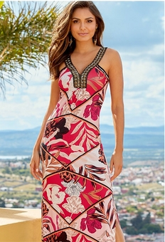 model wearing a red and white embroidered floral maxi dress.