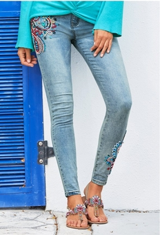 model wearing paisley embroidered jeans with jewel studded sandals.