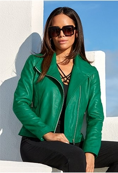model wearing a green leather jacket with a black strappy tank top, black jeans, and statement sunglasses.