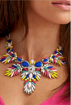 model wearing a multicolored bright statement necklace.