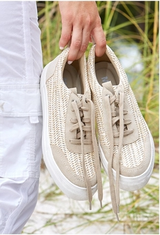 model holding a pair of raffia lace up sneakers.