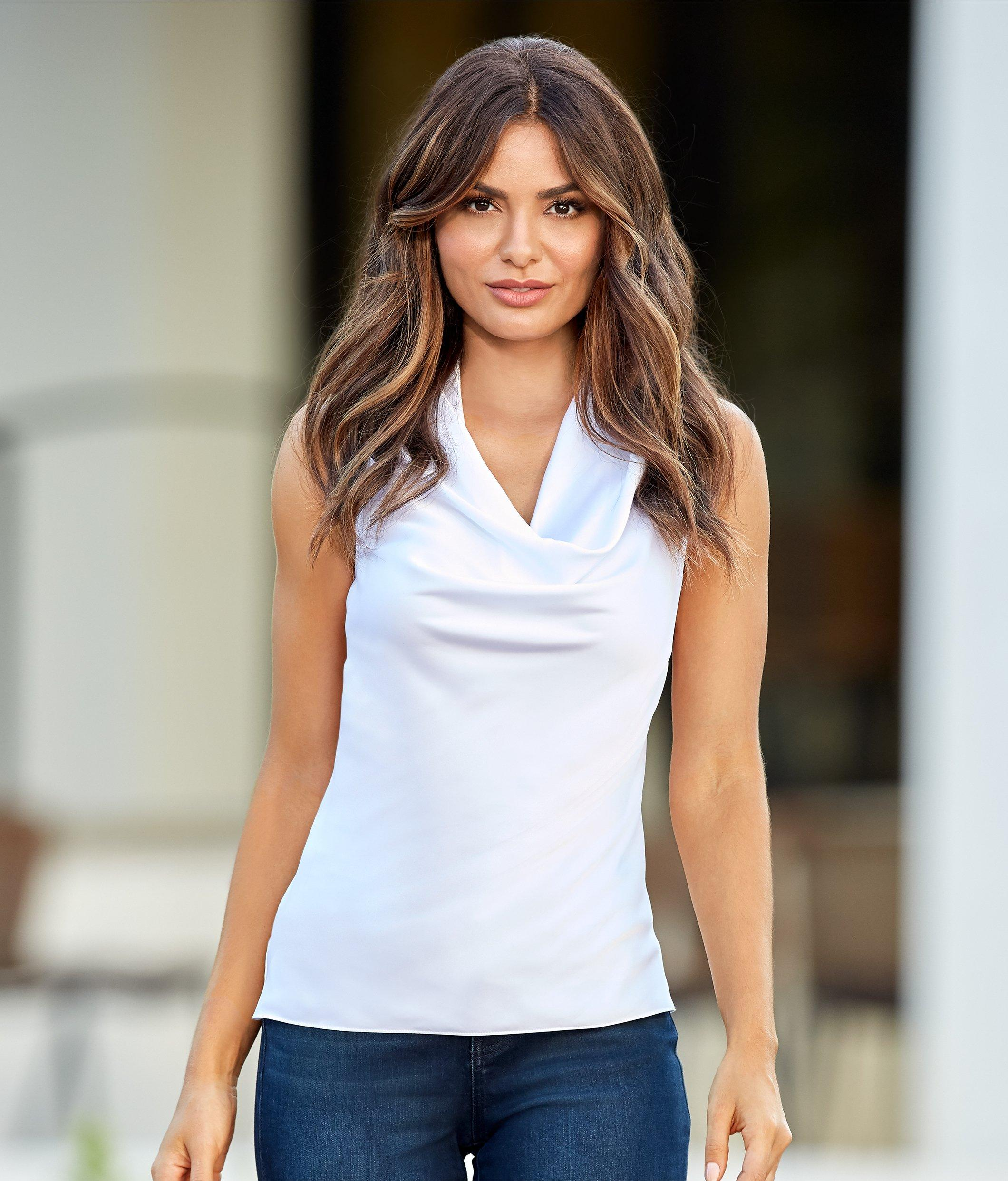 model wearing a white sleeveless cowl neck top with jeans.