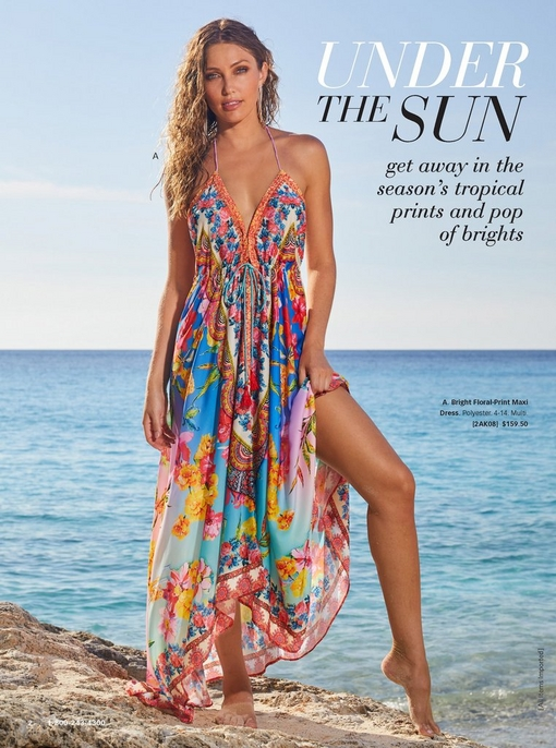 model standing on the beach wearing a bright floral-print maxi dress and long dangle earrings.
