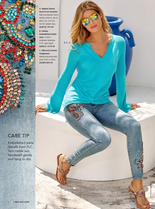 model sitting on ledge wearing a light blue knot-front sweater, paisley embellished jeans, crystal embellished sandals, and mirrored aviator sunglasses.