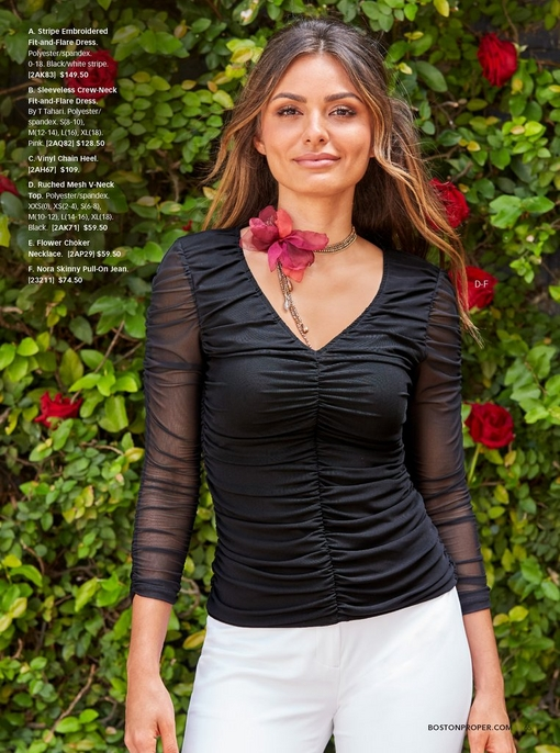 model standing in front of rose bush wearing a black ruched top with white pants and a floral choker necklace.