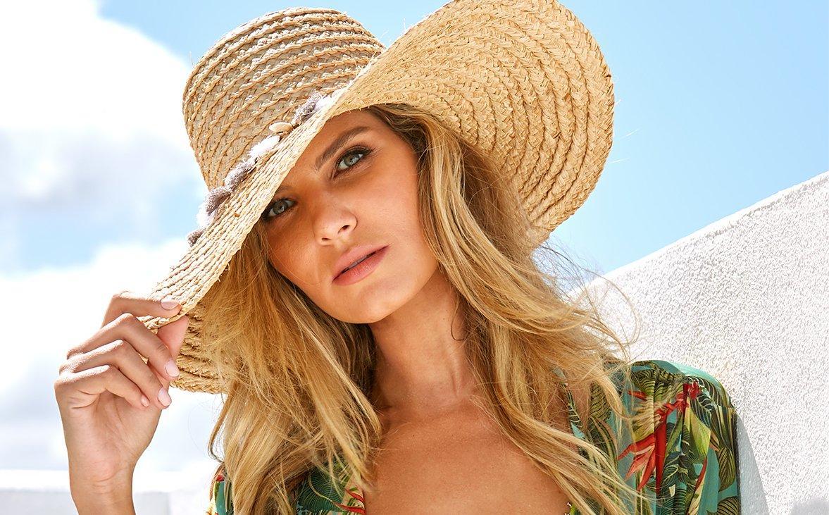 model wearing a raffia beach hat with shell embellishments.