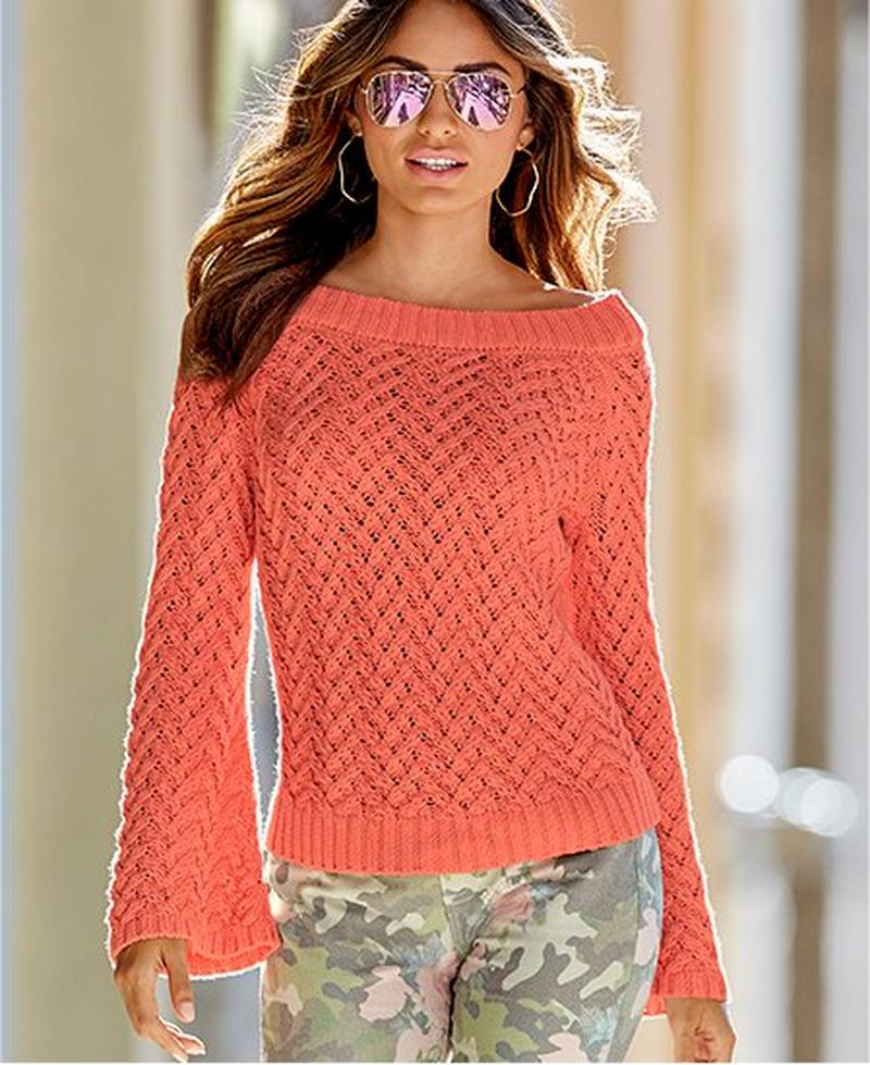model wearing blush pink bell-sleeve sweater with pink floral camo jeans and aviator sunglasses.