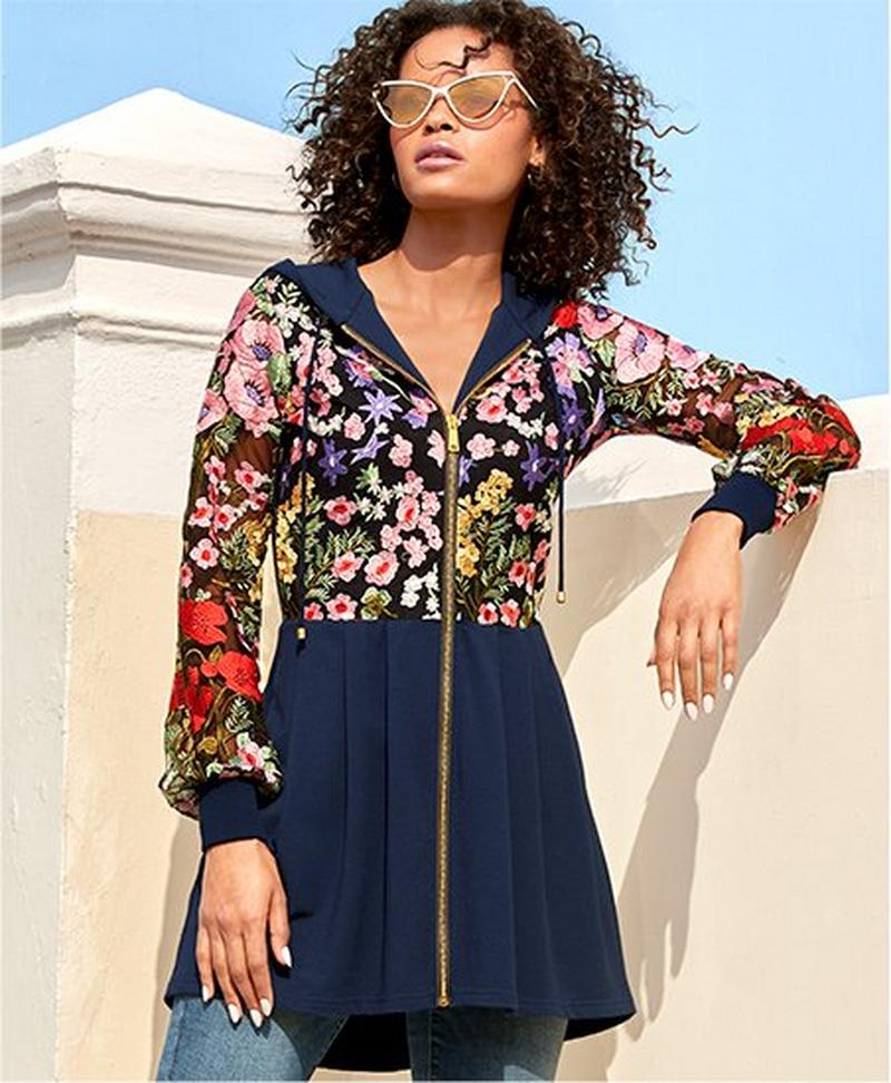 model wearing navy zip-up jacket with floral embroidery.