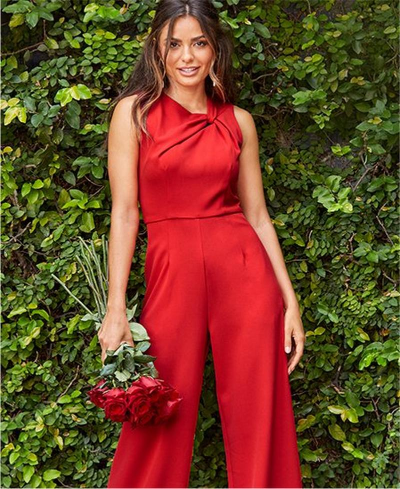 model wearing sleeveless red ruched jumpsuit while holding a bouquet of roses.