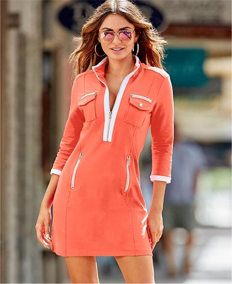 model wearing pink chic zip dress with white piping and aviator sunglasses.