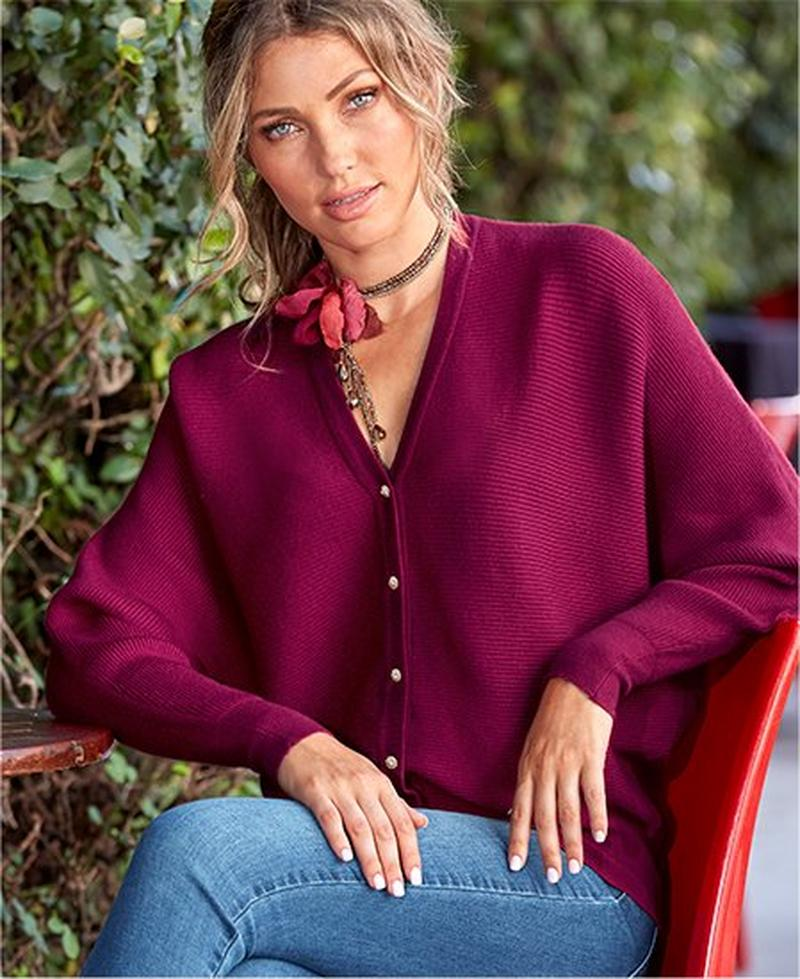 model wearing beet red sweater with jeweled buttons, a floral choker necklace, and jeans.