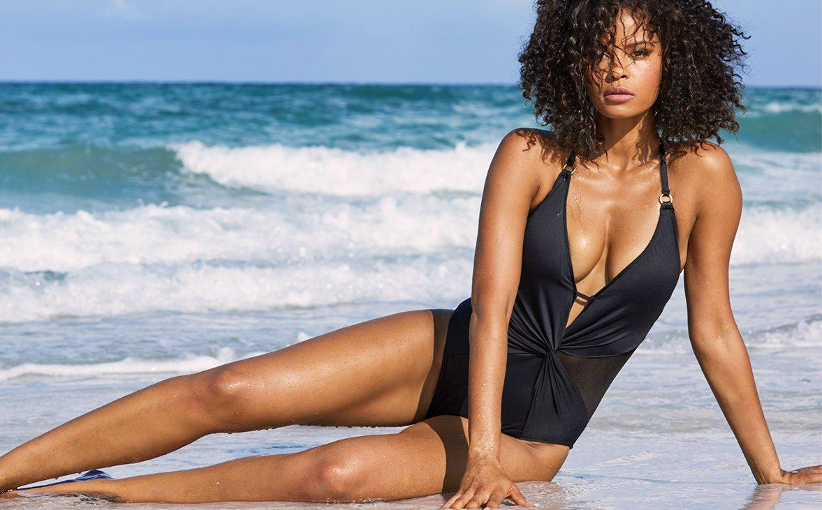 model lounging on the beach in a black one piece swimsuit with a plunging neckline.