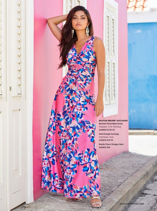 model wearing a ruched pink dress with blue flowers allover and shell dangle earrings.