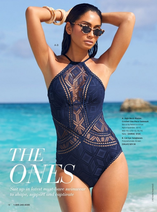 model on the beach wearing a navy crochet one-piece swimsuit and cat eye sunglasses.