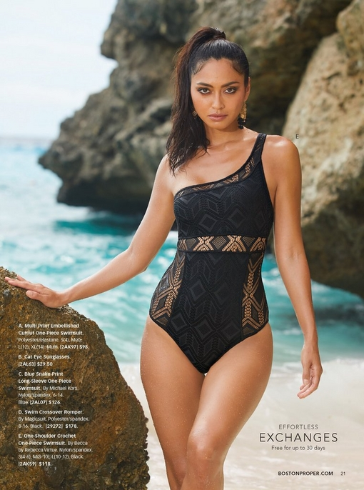 model on a rocky beach wearing a lacy black one-piece, one-shoulder swimsuit.