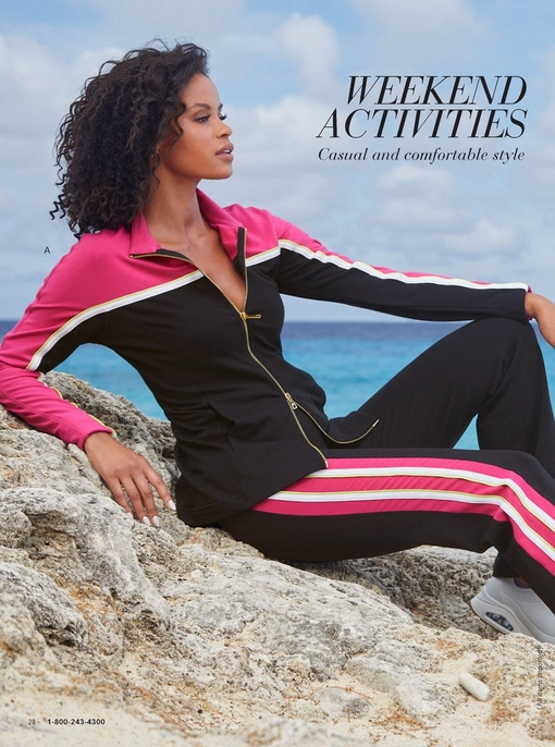 model lounging on a rock at the beach wearing a black, pink, and white colorblock warm up.