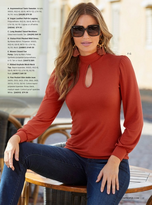 model wearing a ribbed keyhole mock-neck top in rust, denim, large statement sunglasses, and rust colored tassel earrings.