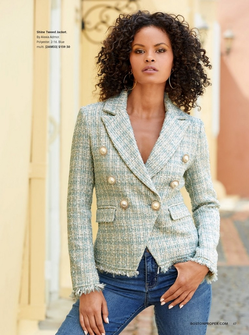 model wearing a pastel green tweed jacket with large gold buttons and blue jeans.