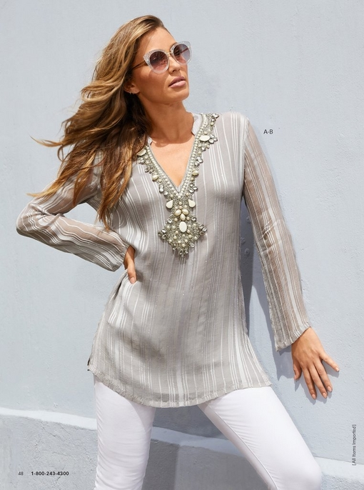 model wearing a gray, embellished tunic with white pants and glitzy sunglasses.