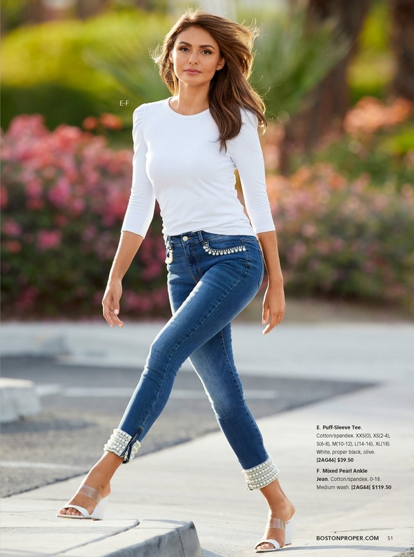 model wearing a puff sleeved white top with pearl embellished jeans and vinyl wedges.