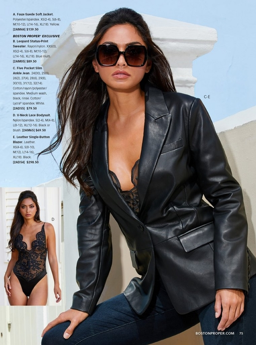 model wearing a faux-leather black blazer, a black lace bodysuit, jeans, and statement sunglasses.