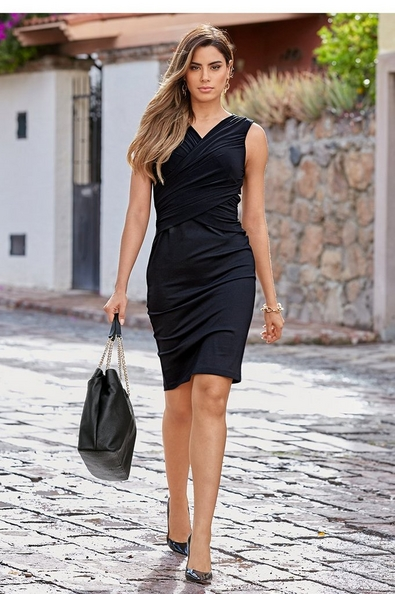 model wearing a black ruched sleeveless dress and black pumps while holding a black handbag.