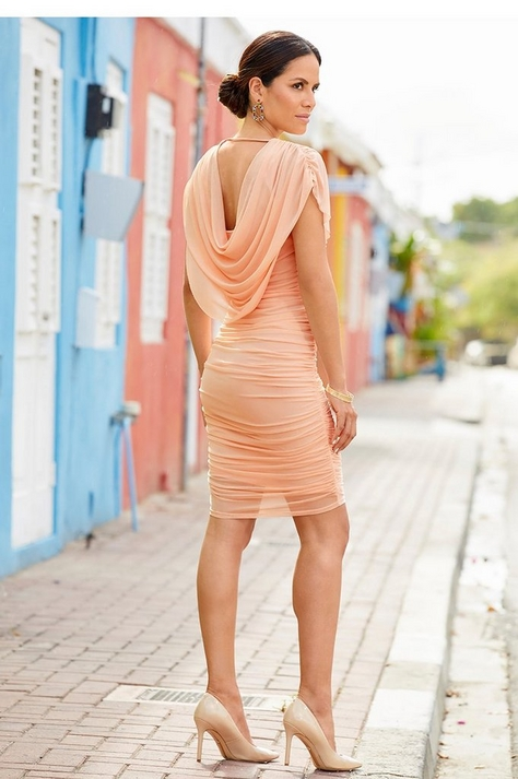 model wearing a blush ruched dress with a draped back and nude pumps.