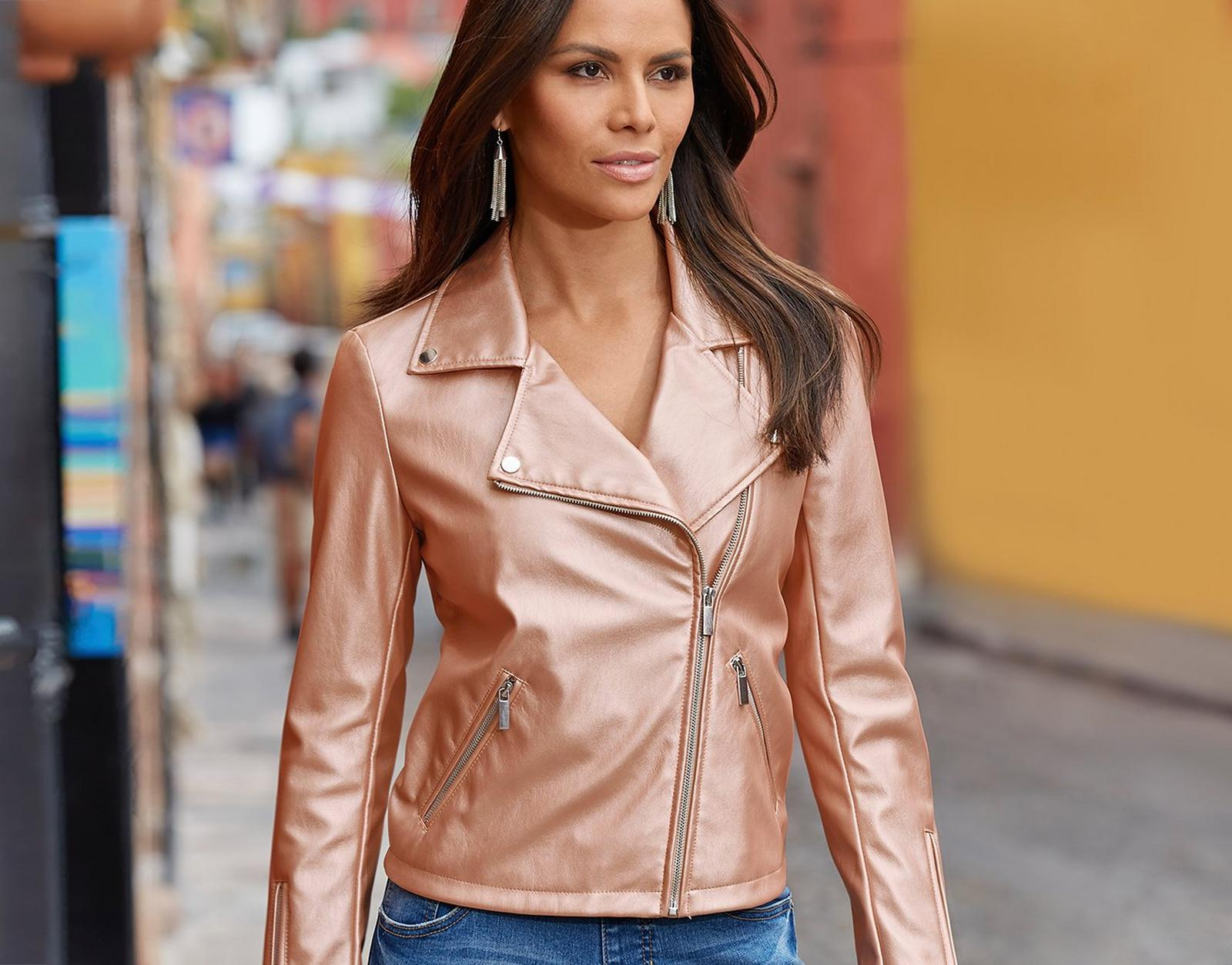 model wearing a rose metallic moto jacket, dangle earrings, and jeans.